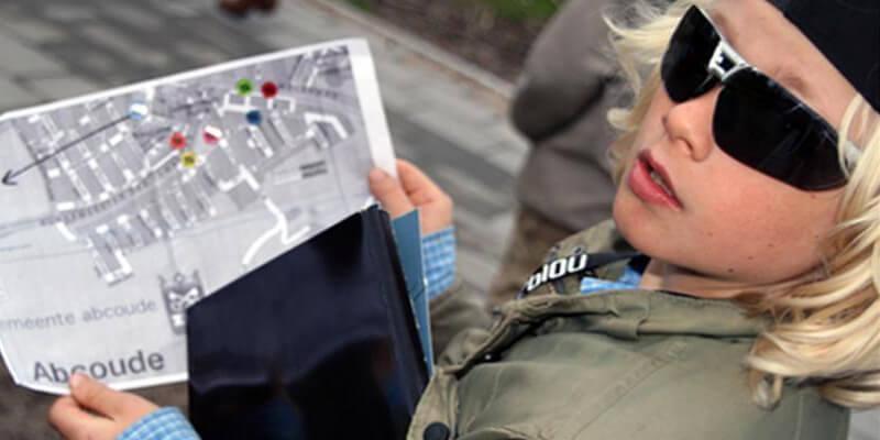 Een jongen met de plattegrond voor de speurtocht
