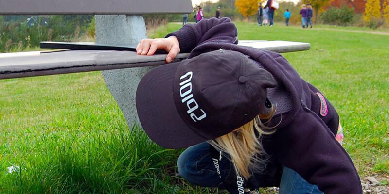 Jongen zoekt onder een bankje naar een aanwijzing